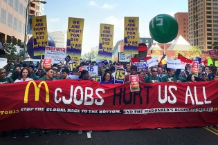 "fight for fifteen rally. ""McJobs hurt us all"" banner in front"